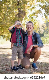 Happy mature father kneeling by boy looking through binoculars in forest
