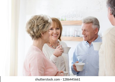 Happy mature friends holding drinks while talking in living room at home