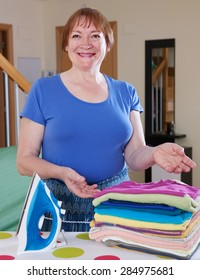 Happy mature housewife ironing with iron at home