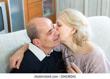 Happy mature husband and loving wife cuddling on couch at home