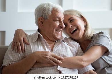 幸せな成熟した夫と妻は、家のソファに座って抱き寄り、抱き寄せ、介護の愛情を示し、笑顔の老夫婦はソファでリラックスし、優しいロマンチックな家族の週末を一緒に楽しむ