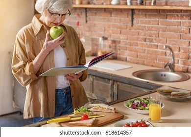 Happy mature lady cooking at home