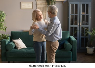 Happy mature loving couple dancing in living room relaxing at home on weekend together, smiling grey-haired elderly husband and wife spend time waltz hugging embracing, spouses enjoy romantic date