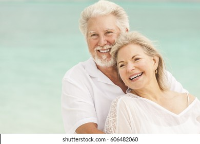 Happy mature male female Caucasian couple living a healthy outdoor leisure lifestyle on a Caribbean beach