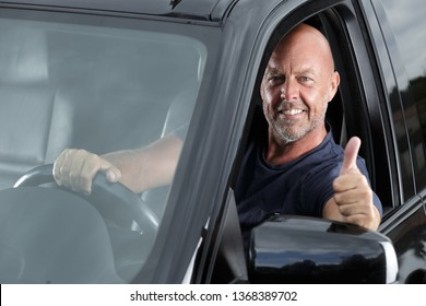 happy mature male motorist giving a thumbs up