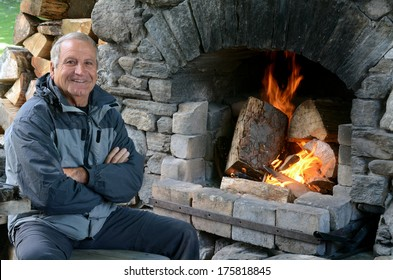 Happy mature man (70's) smile near awarm outdoor fireplace.