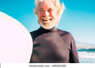 happy mature man with black wetsuit and surftable at the beach ready to go surf - close up of senior smiling and laughing with the sea or ocean at the background