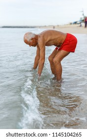 Happy mature man checks the water temperature on the beach
