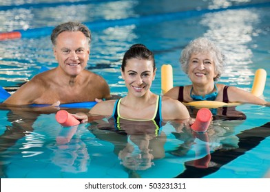 Happy mature man and old woman doing aqua aerobics with foam rollers in swimming pool. Senior couple smiling with swim noodles doing aqua fitness. Smiling trainer with mature class doing aqua gym.