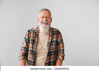 Happy mature man on grey background