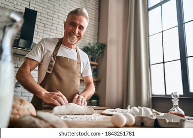 Happy mature man preparing the dough while kneading the dough on a wooden counter with flour and a roll pin. Baking concept