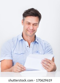 Happy Mature Man Reading Paper Holding In Hands