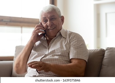 Happy mature man sit on couch at home talking on cellphone with fast unlimited mobile provider connection, smiling elderly male senior grandfather have call with relatives use smartphone internet