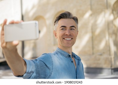 Happy mature man taking selfie using smartphone. Smiling blogger influencer streaming video outdoors