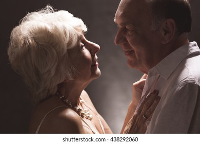 Happy mature man and woman looking in their eyes, dark background