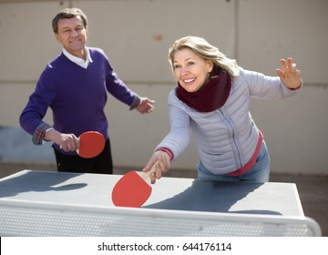 Happy mature man and a woman playing table tennis and smiling