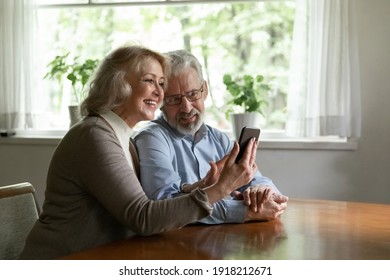 Happy mature man and woman using phone together, browsing apps, happy elderly wife showing funny video or news to husband, aged couple making video call, chatting or shopping online at home