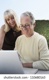 Happy mature man with woman working on laptop