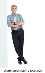 Happy Mature Manager With Arms Crossed Leaning Against Blank Placard Looking At Camera Isolated on White Background