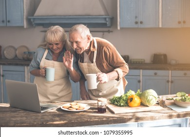 Happy mature married couple are speaking in internet with someone. Woman is waving hand to laptop camera and smiling. Man is looking at screen with interest while holding cup of tea