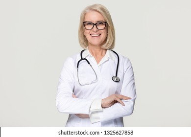 Happy mature middle aged woman doctor medical nurse portrait, smiling old senior female physician practitioner in uniform with stethoscope isolated on white grey studio background, healthcare concept