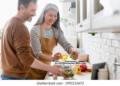 Happy mature middle-aged couple cooking vegetable vegetarian salad together in the kitchen, helping in preparation of food meal. Family moments, domestic homemade food