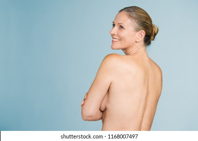 Happy mature naked woman standing showing her back isolated over grey background. Back view of senior woman with arms folded standing nude showing upper body back.