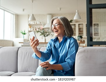 Happy mature old 60s woman holding smartphone using mobile phone app for video call, laughing while watching funny video, feeling excited winning online lottery bid on cellphone sits on couch at home.