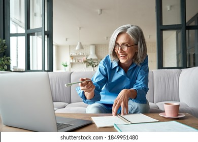 Happy mature older woman video calling on laptop working from home. Smiling 60s middle aged businesswoman talking by conference online virtual chat using computer at home office sitting on couch. - Shutterstock ID 1849951480