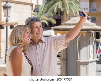 Happy mature senior couple of tourists posing for a on their mobile phone as a memento of their tropical summer vacation