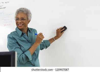 Happy mature teacher explaining a lesson in classroom