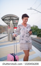 Happy Mature Tourist Woman Using Phone While Waiting At The Train Station