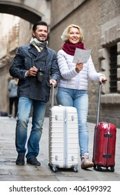 Happy mature tourists walking by street with suitcases, camera and map