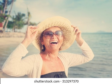 Happy mature woman of 50 years on the beach
