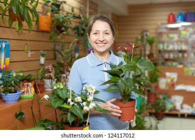 Happy mature woman with anthurium surrounded by different flowers in flower store