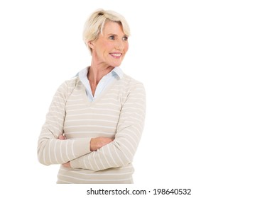 happy mature woman with arms crossed looking away