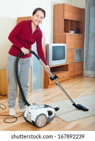 Happy mature woman cleaning with vacuum cleaner on parquet floor