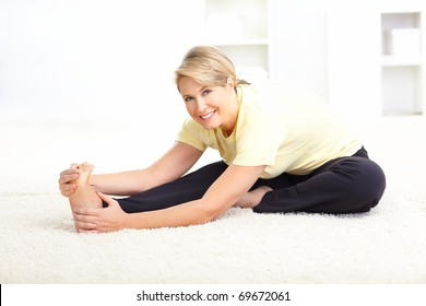 Happy mature woman doing yoga