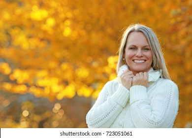 Happy mature woman in front of golden autumn leaves enjoys leisure time