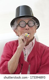 happy mature woman with funny big eye-glasses , party hat and noise maker