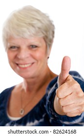 Happy, mature woman giving thumbs up for approval.