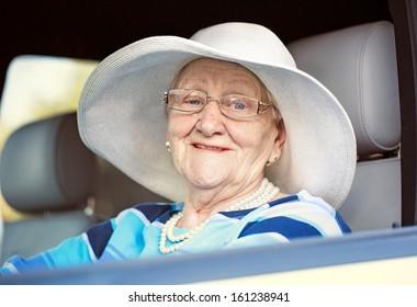 happy mature woman in glasses driving car