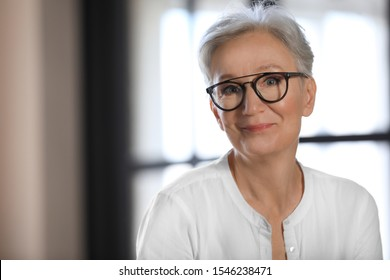 Happy mature woman in glasses indoors, space for text. Smart aging