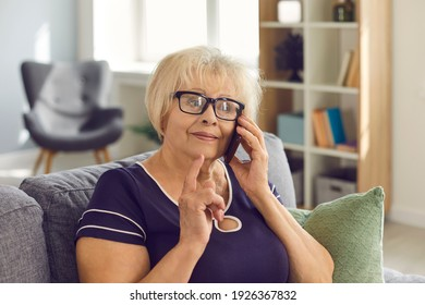 Happy mature woman in glasses talking to relatives on mobile sitting on couch at home. Wise mother-in-law having phone conversation with her daughter-in-law, listening to news and sharing advice