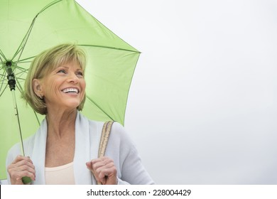 Happy mature woman with green umbrella looking away against clear sky