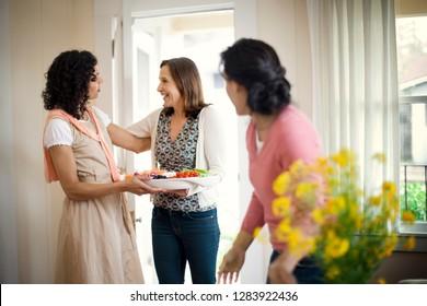Fröhliche reife Frau, die ihre Nachbarn begrüßt.