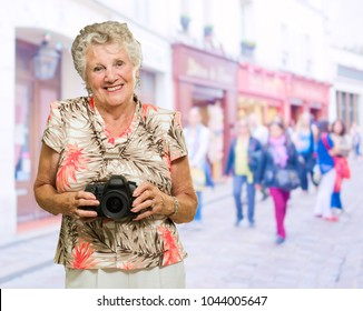 Happy Mature Woman Holding Camera, Outdoors