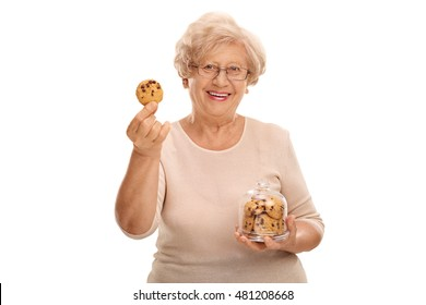 Happy mature woman holding a cookie and a jar full of cookies isolated on white background