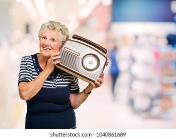 Happy Mature Woman Holding Radio, Indoors