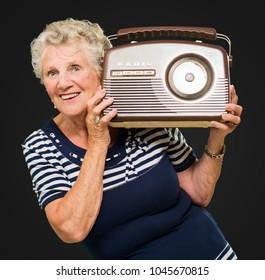 Happy Mature Woman Holding Radio Isolated On Black Background